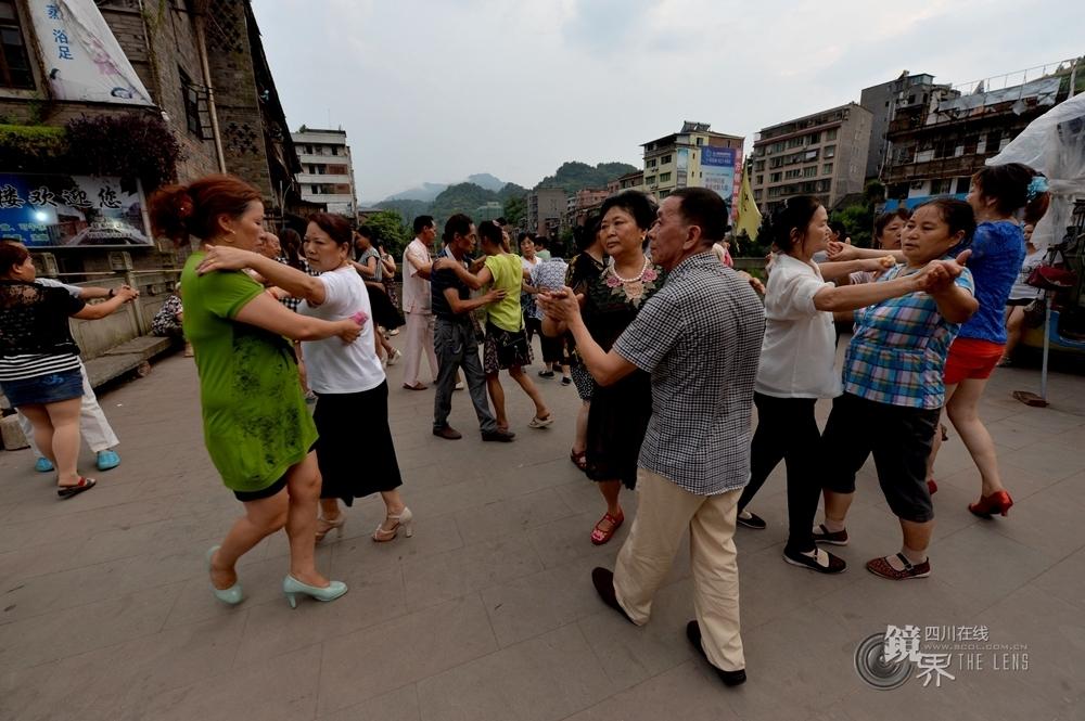 富宝古镇场外桥头上,每到傍晚,这里就是富宝居民纳凉、休闲的地方,音乐声中,居民们会两两成对的跳起交谊舞,哪怕脚穿草鞋也跳得自在。
